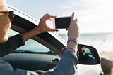 happy young woman in car with smartphone at sea