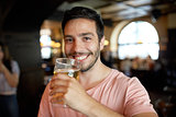 close up of happy man drinking beer at bar or pub