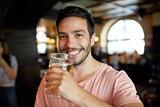 close up of happy man drinking beer at bar or pub