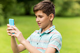 boy with smartphone playing game in summer park