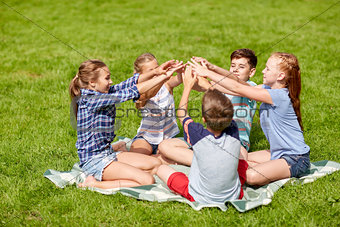 group of happy kids putting hands together