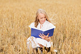 smiling young woman reading book on cereal field