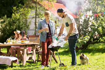friends making barbecue grill at summer party