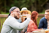 man drinking beer with friends at summer party