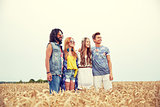 smiling young hippie friends on cereal field