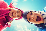happy little boy and girl faces over blue sky