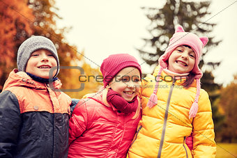 group of happy children hugging in autumn park