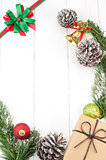 Christmas background with decorations and gift box on white wooden board.