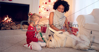 Mom and daughter in sweaters play with pet dog