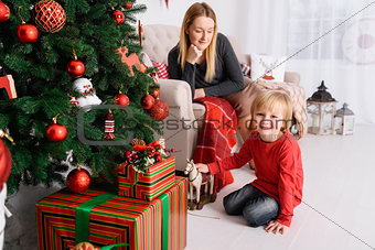 Mom plays with her son near Christmas tree