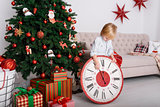 Boy with a big clock in Christmas tree