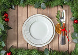 Christmas table layout, red tape with a cinnamon stick, rosmarin and a slice of dry orange