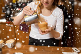 close up of woman making coffee at shop or cafe