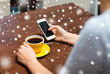 woman with smartphone drinking coffee at cafe