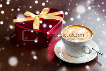 close up of gift box and coffee cup on table