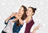 happy teenage girls hugging and showing peace sign