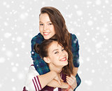 smiling pretty teenage girls hugging over snow