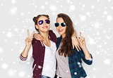 smiling teenage girls in sunglasses showing peace