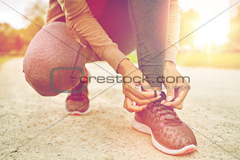 close up of woman tying shoelaces outdoors