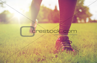 close up of exercising woman legs on grass in park