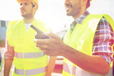 close up of builders in vests with walkie talkie