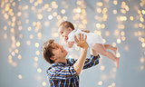 happy young father playing with baby over lights