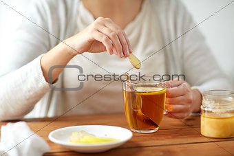 close up of ill woman drinking tea with ginger