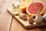 garlic, grapefruit, ginger, and orange on board