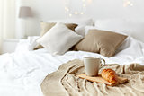 coffee cup and croissant on plaid in bed at home