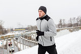 man in earphones running along winter bridge