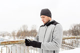 man in earphones with smartphone on winter bridge