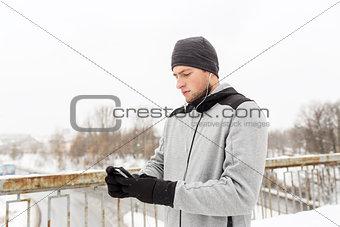 man in earphones with smartphone on winter bridge