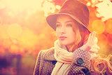 Fashion Woman in Hat on Orange Autumn Background