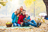 Happy young family with two boys in forest