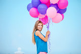 Beautiful young woman with a bunch of balloons