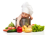 Little boy in chef's hat reaching for bell pepper while sitting in large casserole
