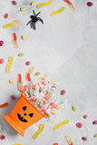 Halloween bucket with candies and jujube on gray concrete backgr