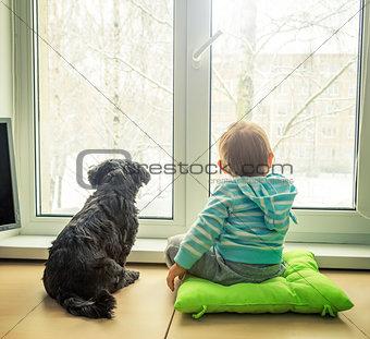 Baby with Dog Looking through a Window in Winter