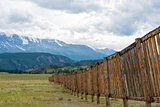 Long wooden fence in a field. In the distance the mountains.