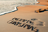 text merry christmas in the sand of a beach