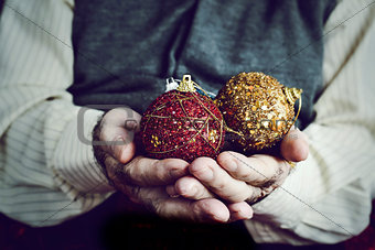 old man with christmas balls in his hands