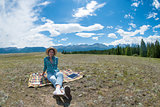 Beautiful young lady sit on a field in the mountains outdoors background.