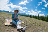 Young woman reading book and sitting in a field. Mountains background.