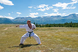 Man in white kimono and black belt training karate on mountain background.