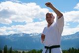 Man in white kimono and black belt training kung-fu, karate or aikido on mountain background.