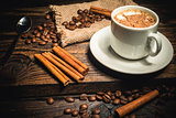 cup of coffee and ingredients on a wooden background