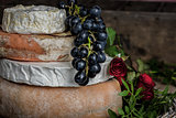 aged cheese wheels concord grapes with long stem red roses