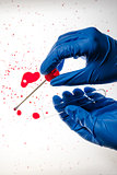 Forensic technician taking DNA sample from blood stain