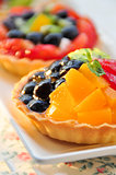Two fruit tart on white dish, close up