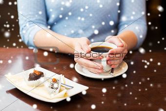 close up of woman holding coffee cup and dessert